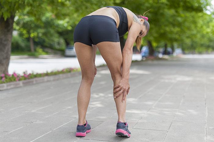 Donna colpita da crampo al polpaccio mentre si allena