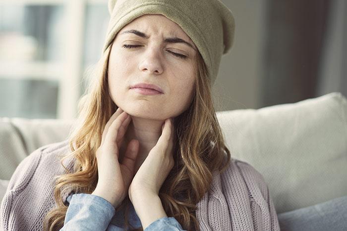 Giovane donna avvolge con le mani la gola infiammata