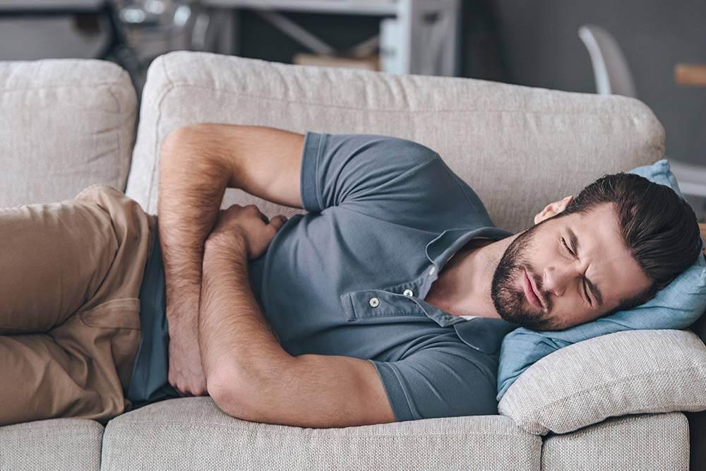 Uomo disteso afferra l'addome a causa dei dolori da mal di stomaco